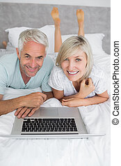 Relaxed mature couple using laptop in bed - Portrait of a...