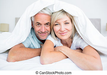 Portrait of a mature couple lying in bed - Closeup portrait...