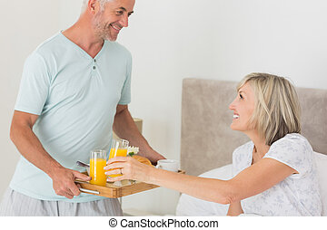 Man serving woman breakfast in bed - Mature man serving...