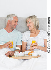 Happy mature couple having breakfast in bed - Portrait of...