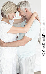 Loving mature couple with arms around - Side view of a...
