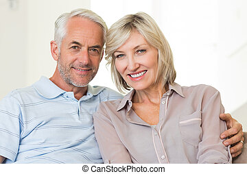 Smiling mature couple sitting on sofa with arm around -...
