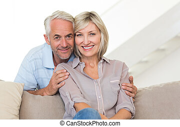 Portrait of a smiling couple sitting on sofa - Portrait of a...