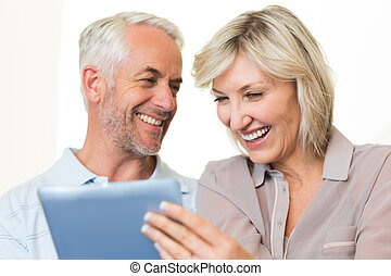 Closeup of cheerful mature couple using digital tablet -...