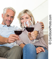 Smiling mature couple with wine glasses sitting on sofa -...
