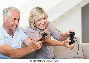 Cheerful mature couple playing video game on sofa - Portrait...