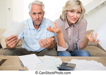 Tensed mature couple with bills and calculator at home -...