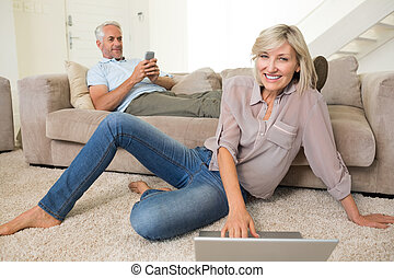 Couple with laptop and cellphone in living room at home -...