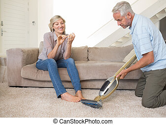 Woman filing nails while man vacuuming area rug - Woman...