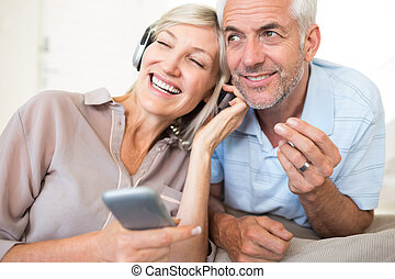 Mature couple with headphones and c - Cheerful mature man...