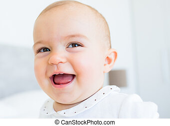 Closeup portrait of a smiling cute baby over blurred...