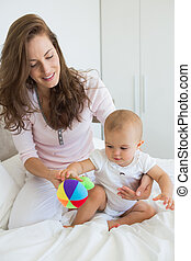 Mother and baby sitting with toy on bed - Relaxed mother and...