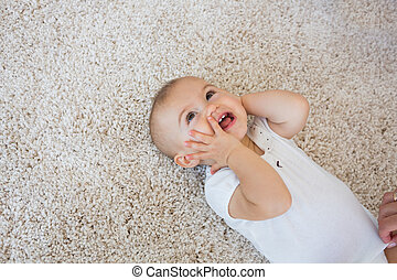 Happy cute baby lying on carpet - High angle view of a happy...