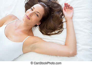Portrait of pretty young woman lying in bed