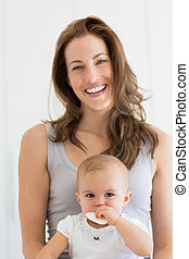Closeup portrait of a smiling mother and baby over white...