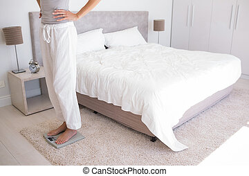 Low section of a woman standing on scale in bedroom - Side...