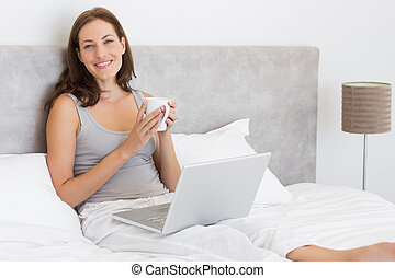 Relaxed young woman using laptop in bed