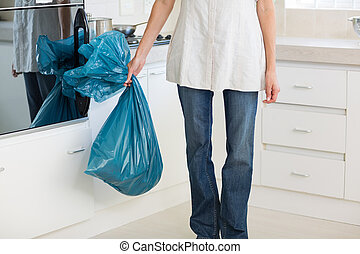 Low section of woman carrying garbage bag in kitchen - Low...