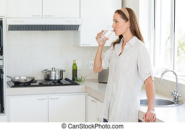Side view of a woman drinking water in kitchen - Side view...
