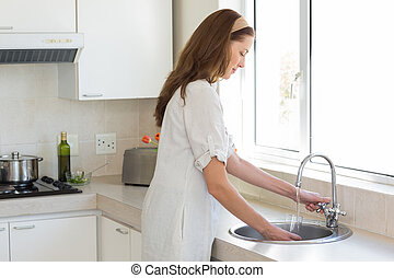 Woman washing glass at washbasin in kitchen - Side view of a...