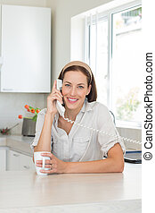 Smiling woman with coffee cup using landline phone in...