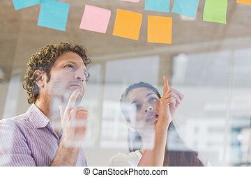 Business people looking at adhesive notes - Businessman and...