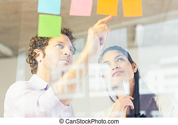 Business people reading adhesive notes - Businessman and...