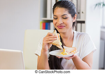 Businesswoman eating sandwich in lunch break