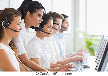 Manager assisting her staffs in call center - Side view of...