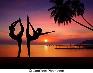 Silhouette of Yoga girls in sunset