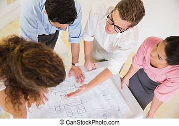 Business people discussing over blueprint