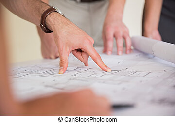 Businessman pointing on blueprint - Cropped image of...