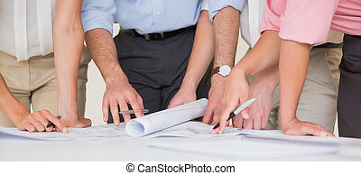Business people working on blueprint - Mid section of...