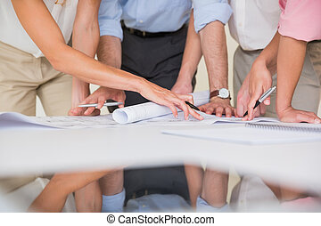 Business people studying blueprint - Mid section of business...