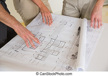 Business people wotking on blueprint - Mid section of...