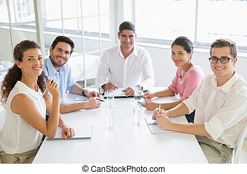 Smiling business people at conference table - Portrait of...