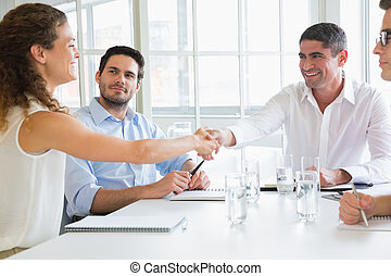 Business partners shaking hands at conference table in...
