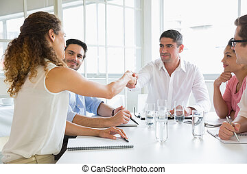 Business people shaking hands at conference table in office