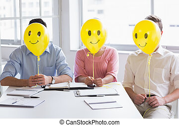 Business people holding balloons in front of face in meeting...