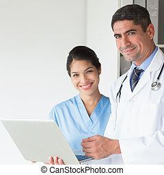Confident doctor and nurse using laptop - Portrait of...