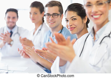 Confident nurse and doctors applauding - Portrait of...