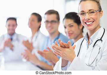 Happy doctor and team clapping - Portrait of happy female...