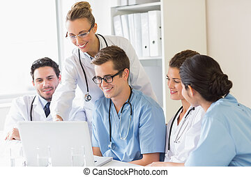 Smiling doctors and nurses discussing over laptop in...