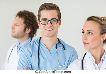 Portrait of confident male nurse with doctors in hospital