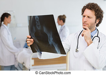 Concentrated doctor examining Xray