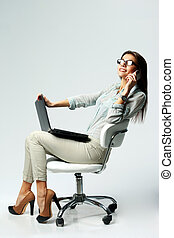 Young happy businesswoman using laptop and phone on gray...