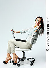 Young happy businesswoman sitting on the chair with laptop...