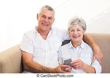 Smiling couple using mobile phone