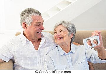 Senior couple taking selfie through cellphone - Loving...