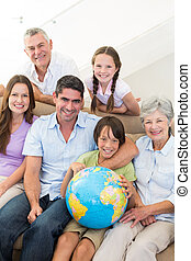 Smiling multigeneration family with globe - Portrait of...